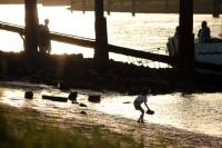 Kind spielt am Strand bei Sonnenuntergang