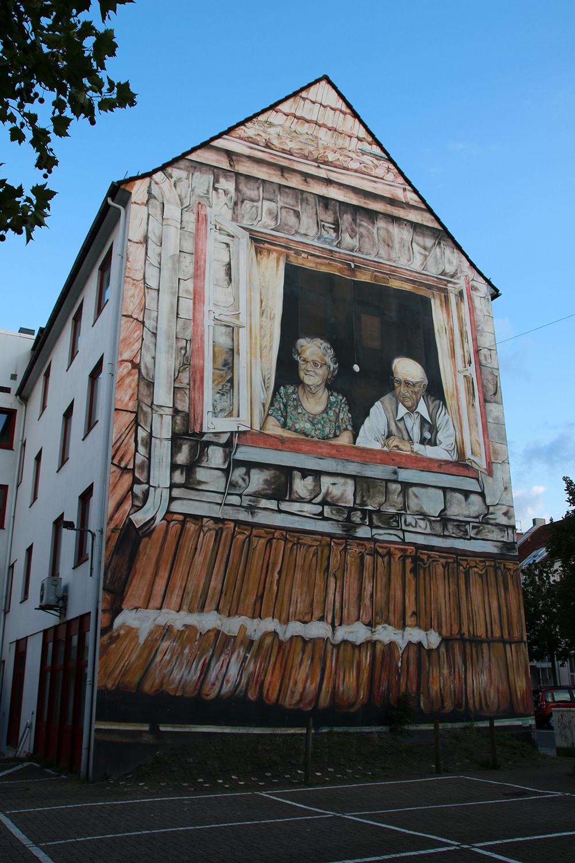 Oma und Opa blicken von einer Hauswand